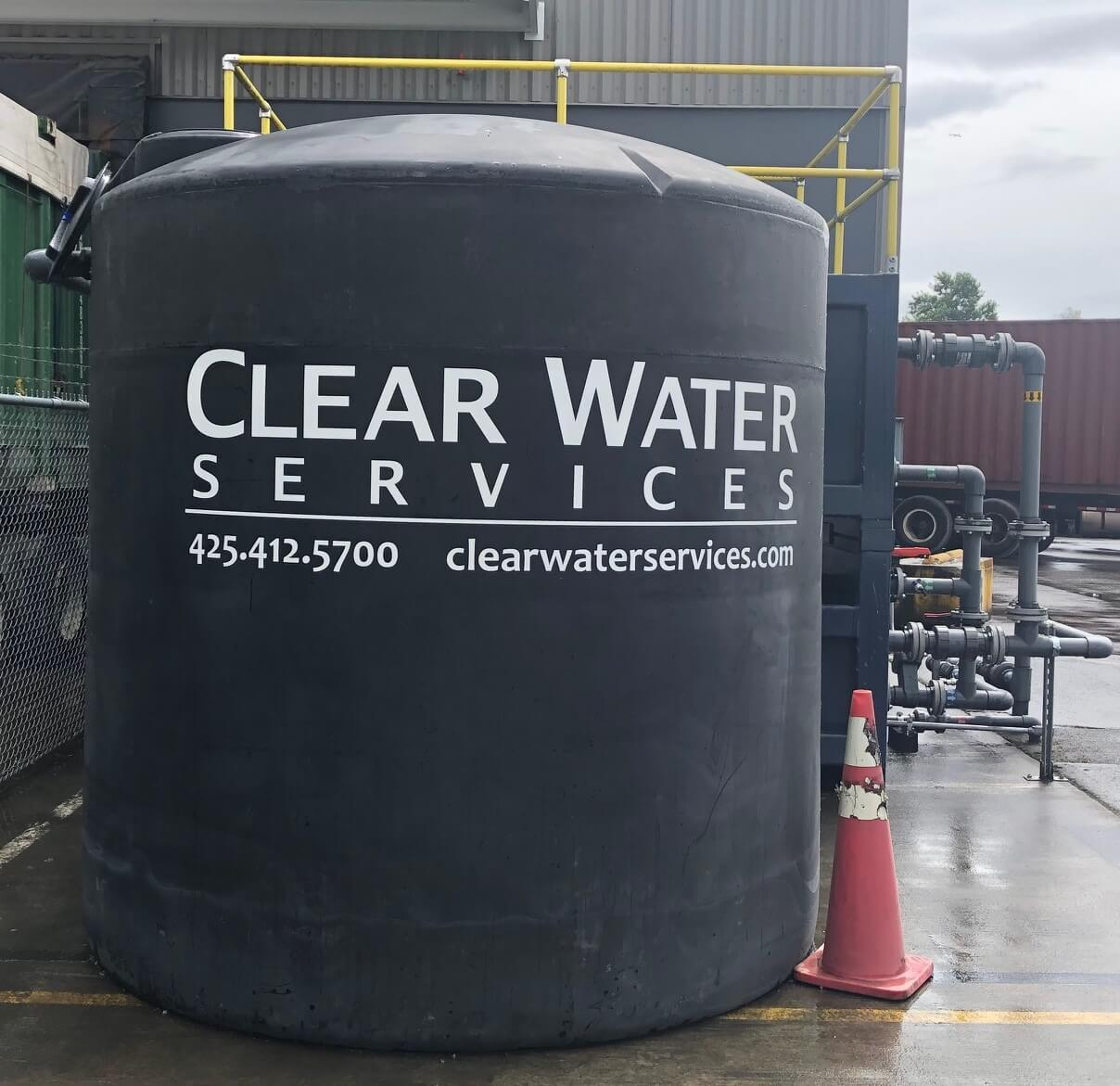 Upright poly stormwater settling tank in front of a Clear Water Services passive treatment system at a materials recovery facility
