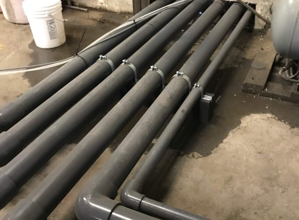 Stormwater treatment conveyance pipes plumbed through a wall at an industrial facility